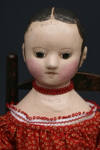 Savannah has a red coral bead necklace and a chemise trimmed in red tatting.
