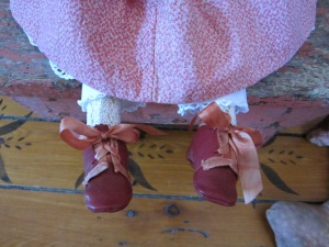 "Miss ""A""'s hand made red leather shoes are trimmed in hand dyed silk ribbons that have been carefully matched to faded antique originals."