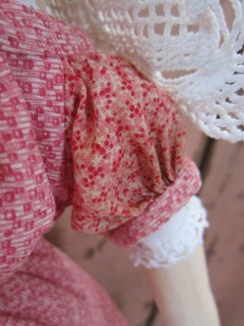 "She has one charming ""make-do"" sleeve, that almost, but not quite matches the rest of her dress fabric.  Her dress has a ""false hem"" made from a third antique ""double pink"" fabric."