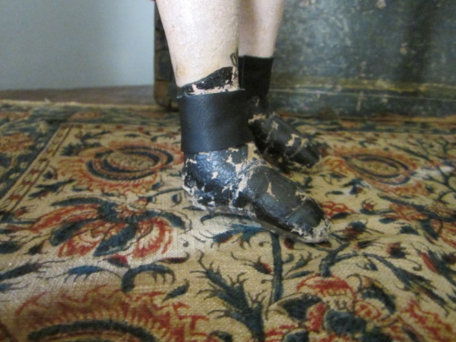 A side view of Izannah's painted boots.  Notice how the top of the boots are higher at the front of the leg and lower in the back.