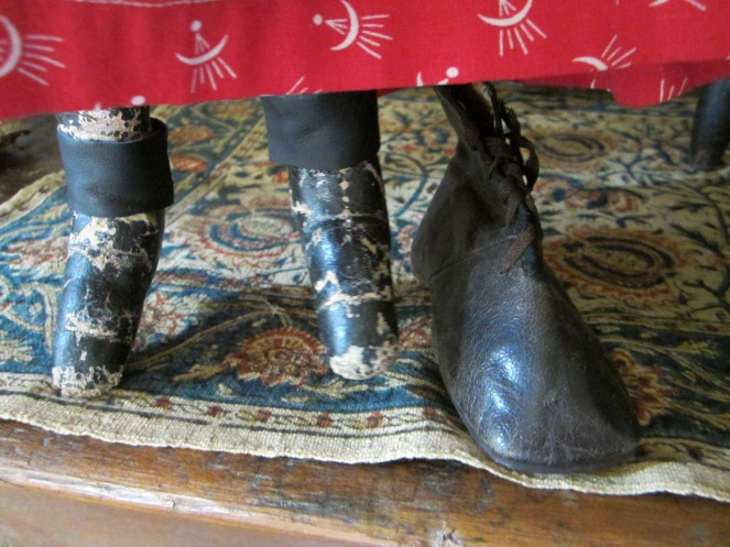 Here you can see the painted version on the doll and the real life child's boot side by side.  The ankles on this Izannah Walker doll have given way over time, with the painted fabric splitting near the ankle seam, where the leg is weaker.  I have conserved the legs by affixing thin bands of leather to the ankles, using rubber cement.  This holds the legs and feet together, but is a repair that can be removed without causing damage to the original antique surfaces beneath.