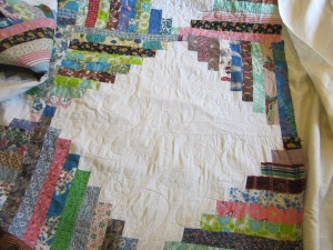 I quilted a vintage c.1960's log cabin quilt top that I have had waiting in my attic for several years.  Jan suggested a free form daisy quilting pattern, which was just perfect for the 60's :)