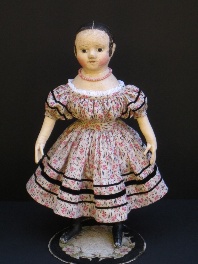 Her dress made from antique pink and black print fabric is adorned with rows ans rows of black velvet ribbon.