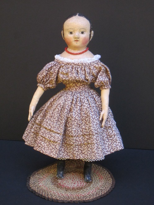 """Isabeau #2 is wearing a dress that I made for her from a mid-1800's brown """"coral"""" pattern print fabric.  The dress has full gathered sleeves, two growth tucks in the skirt and a deep 3 inch hem."""