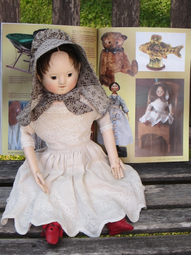 My doll posing with her photo in the Early American Life Craftsman Directory.