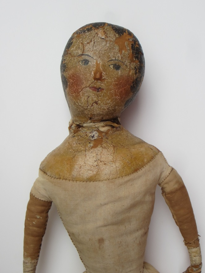 The neck of the doll suffered a lot of wear and tear over the years.  Portions of the painted cloth are missing.