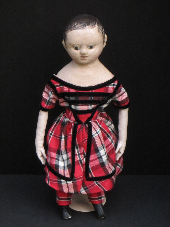 17 inch tall Andrew, dressed in a split skirt red and black plaid dress with black velvet trim, matching breeches, antique linen chemise and black and red painted boots.