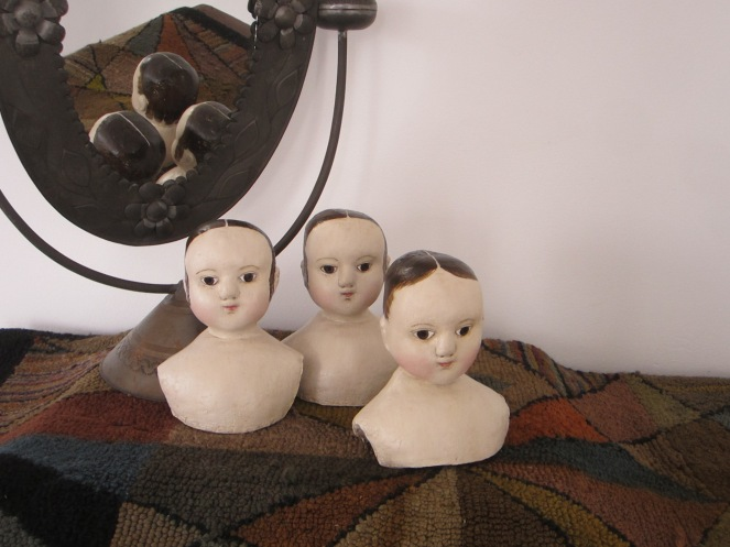 Another photograph showing  the difference between the two in the back, compared o the younger more baby like features of head #1, in the foreground.