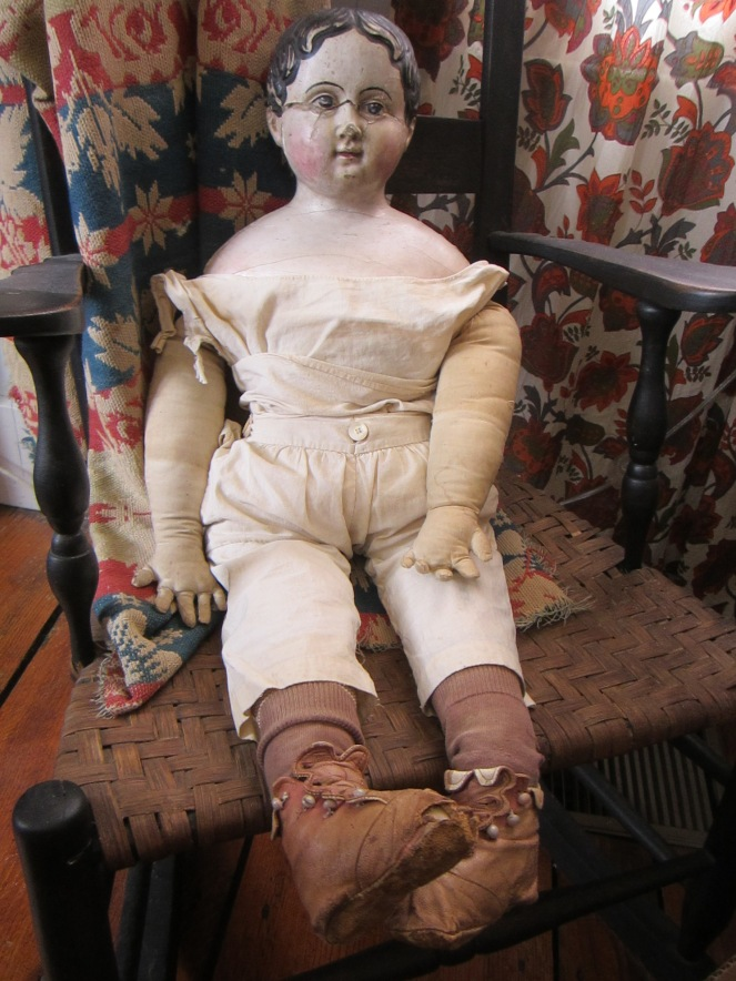 This very large papier-mache doll can wear children's size clothing.