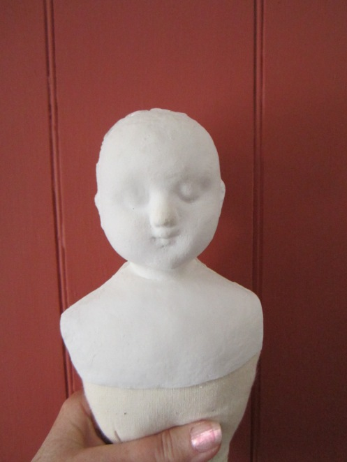 Photo of an uncleaned, unpainted  composition head mounted on a stuffed body with custom fitted shoulders.