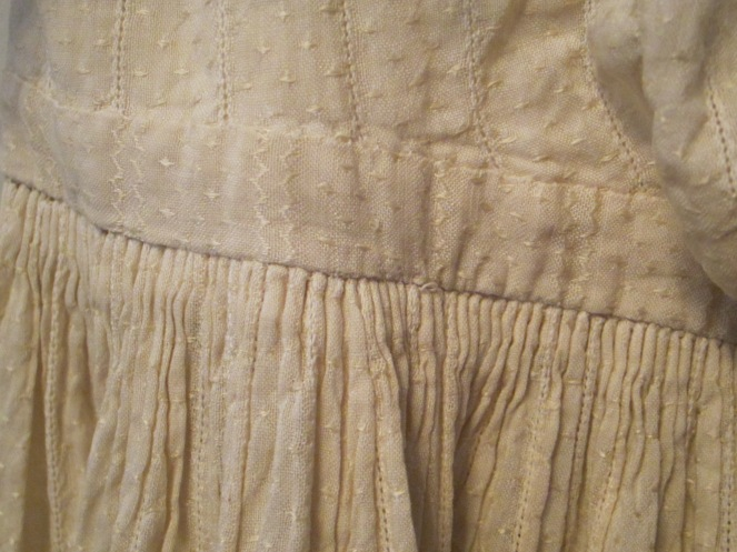 The dress fabric is a woven white on white cotton that has turned to a lovely pale ivory over time. All of the long seams are machine sewn, with the detail work, such as this tiny cartridge pleating done by hand.