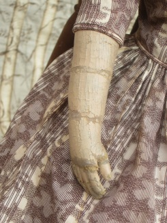 Originl paint and wear marks on her arm. Self piping and cartridge pleating at the waist of her dress.