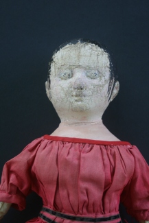 A close up of Lily's face and the bodice of her dress before restoration.