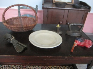 A tiny tin candle holder and silk flags from NH, along with an ironstone plate, tin spoons, a cast iron iron, and a tiny old basket from our stop in Sturbridge, MA.