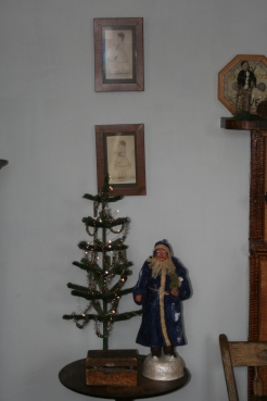 Father Christmas stands watch beside a garlanded tree..