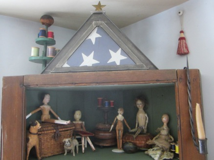 "The little wooden dolls have taken over the ""attic""of the corner cupboard as their sewing room."