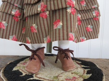 Handmade leather shoes, silk stockings, and growth tucks in her dress...